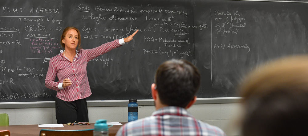 A professor teaches algebra in front of a chalkboard